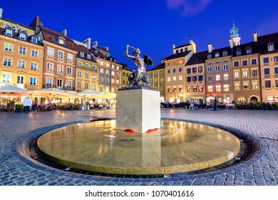 Night view of the bronze statue of Mermaid on the Old Town Market Square of Warsaw, surrounded by colorful old houses, Poland.