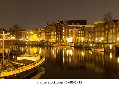 Night view of buildings in Amsterdam reflected in a canal,  Holland