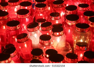 A night view of burning candles lit for the deceased family members and friends lined up on the floor at cemetery on All Saints day.