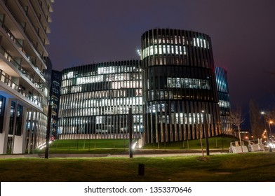 Night view of business glass skyscrapers with lightning windows. Working people in buildings in the evening