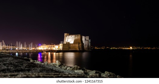 Night view of Castel dell'Ovo over the sea in Naples, Italy. Dark background.