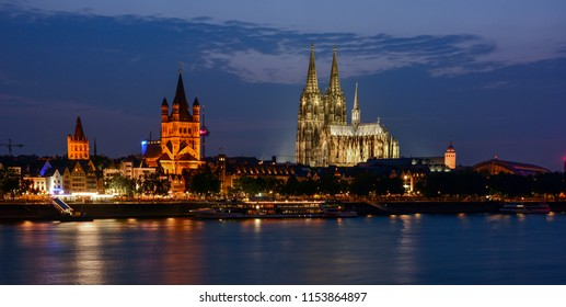 Night view of the center of Cologne, Germany, with the Rhine, the famous gothic Cologne Cathedral (Kölner Dom), the romanesque Great St. Martin Church and the tower of the Rathaus (city hall)