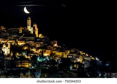 Night view of Cervo Cathedral and its churches with moon rising in background, Liguria, Italy. A black night over mediterranean sea. Il paese di Cervo di notte al sorgere della Luna.