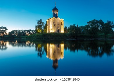 Night view of the Church of the Intercession on the Nerl with a reflection in the water.