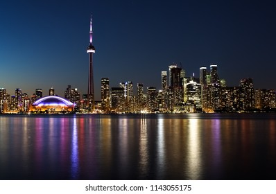 night view of a city with reflection of the lights in the water
