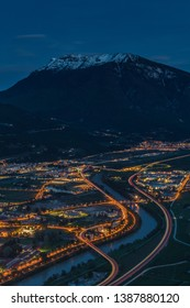 Night view of the city of Trento, Italy with snow capped mountain in background. Night view of a city between mountains and river. High dynamic picture of a city at night with snow capped mountain