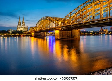 Night View of Cologne Cathedral (Kolner Dom) and Rhine river under the Hohenzollern Bridge, Cologne city skyline at night, North Rhine Westphalia region, Germany.