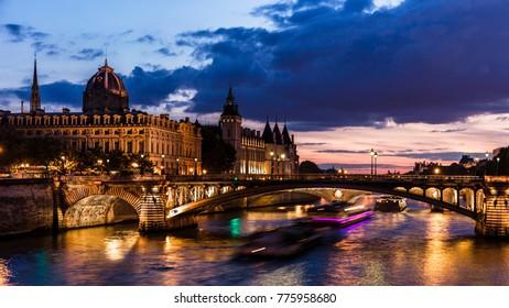 Night view of Conciergerie Castle and Pont Notre-Dame bridge over river Seine. Castle Conciergerie is a former prison and today it is a part of Palais de Justice. Paris, France