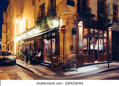 Night view of cozy street with tables of cafe and old bicycle in Paris, France. Architecture and landmarks of Paris. Postcard of Paris