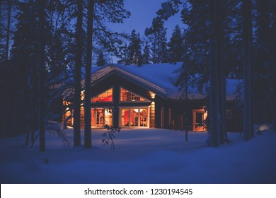 A night view of cozy wooden scandinavian cabin cottage chalet house covered in snow near ski resort in winter with the lights turn on, evening picture