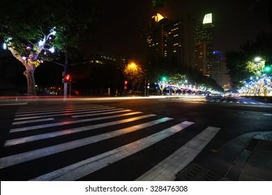 Night view of Crosswalk and pedestrian at modern city zebra crossing street. Blur abstract.