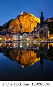 Night view of Dinant town, Collegiate Church of Notre Dame de Dinant over River Meuse and Pont Charles de Gaulle bridge and Dinant Citadel illuminated in the evening. Dinant,  Belgium