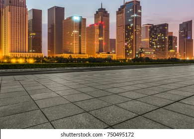 night view of empty pavement front of cityscape and skyline