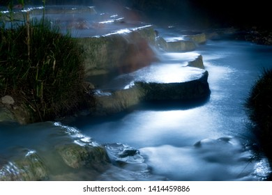 Night view of the famous free spa of the mill in Saturnia in Tuscany, Italy. A series of natural pools of hot water where people relax