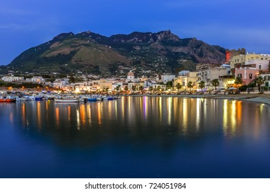 Night view of Forio on the background of Mount Epomeo and reflection in the sea. Italy, Ischia.