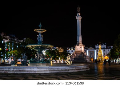 Night view of the fountain and Column of Pedro IV in Lisbon's Rossio square, with the national theatre in the background.