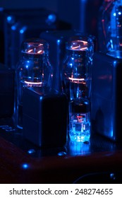 Night view of hi fi amplifier with electronic vacuum tubes with incandescent filament. Grazing blue light