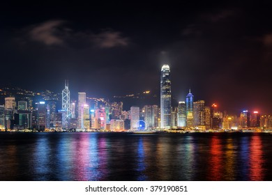 Night view of Hong Kong Island skyline across Victoria harbor from Kowloon side. Skyscrapers on waterfront in downtown of Hong Kong. Hong Kong is a global financial center.