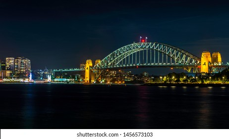 Night view of the iconic Sydney Harbour Bridge and the North Sydney suburb (left), from the Balmain East Wharf ferry terminal. Features plenty of colorful lighting with reflections from the water.