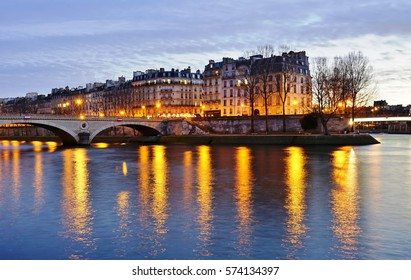 Night view of the Ile Saint Louis island and the Seine River in Paris, France