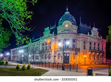 night view of illuminated building of library in bulgarian city rousse - ruse.