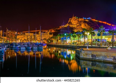 Night view of illuminated pier in spanish city Alicante, which is surrounded by marina from one side and a belt of restaurants and pubs on the other.
