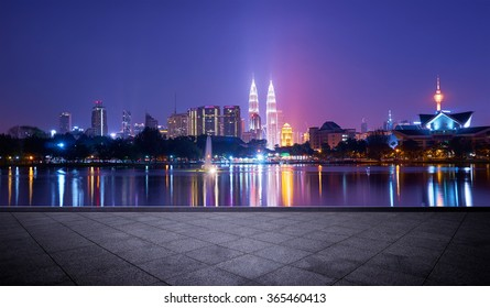 Night view of Kuala Lumpur city with stunning reflection in water and empty concrete square floor
