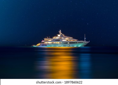 Night view to large illuminated white boat located over horizon, colorful lights coming from yacht reflect on the surface of the the Gulf sea. Shot at blue hour.