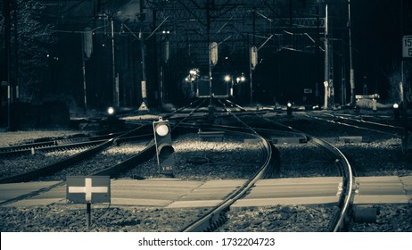 Night view of the long tracks and railway traction, semaphores and track switches. The train can go in two directions.