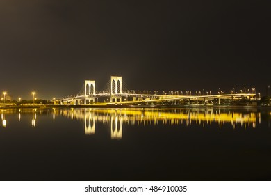 Night view of Macau Praia Grande Bay, in the background is Macau-Taipa bridge lit with golden lights. Macau is popular holiday attraction and growing casino market.