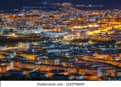Night view of Magadan from a height. Big city in the Far East of Russia. The administrative center of the Magadan region. Many buildings and beautiful street lighting in the dusk.
