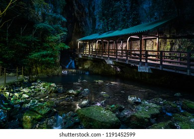 NIght view of the magical and iconic entranceway to Japan's largest limestone cave featuring a covered bridge passing over a waterfall and through a narrow gape into a huge cavern