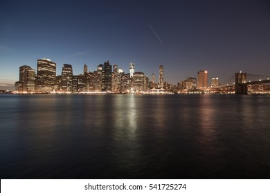 Night view of Manhattan, New York. Reflections of lights and skyscrappers in water. Calm colors, deep blue sky.