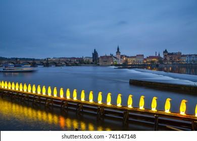 Night view of modern art installation of yellow penguins near Kampa Museum in Prague, Czech Republic.
