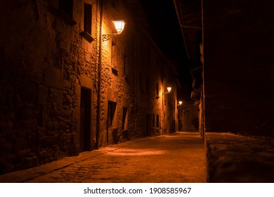Night view of narrow street in old village of Rupit near Barcelona, Spain.Touristic destination concept, empty rustic alley with street lights background.