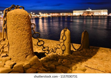 Night view of the Neva in Saint Petersburg, Russia, with the chain fence and the building of Imperial Academy of Arts on the Academy Quay. The Neva river embankments are a popular tourist attraction