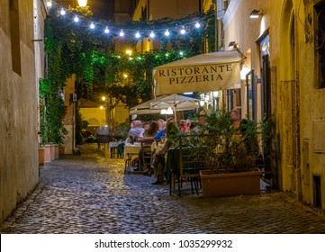 Night view of old street in Trastevere in Rome, Italy. Trastevere is rione of Rome, on the west bank of the Tiber in Rome, Lazio, Italy.  Architecture and landmark of Rome.