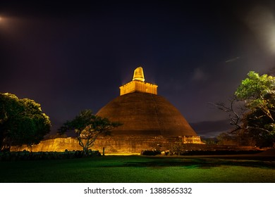 Night view on a huge ancient stupa of Jetavanaramaya, in beams illumination. The stupa is constructed of a brick by the king Mahasena in 300 B.C., on the place where arhat Mahinda preached a sermon.