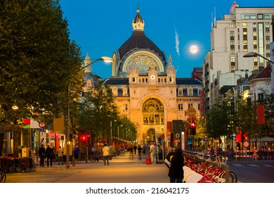 Night view on the street leading to the exterior of Antwerp central railway station at dusk, with deep blue sky and a bright shining moon, and people having a drink at the  terraces along the alley