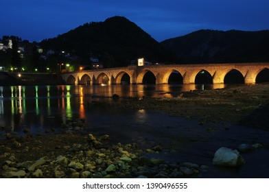 Night view of the Ottoman Mehmed Pasa Sokolovic Bridge in Visegrad, Bosnian mountains. Drina river in Bosnia and Herzegovina. Old stone bridge by night. Colorful reflections in water.