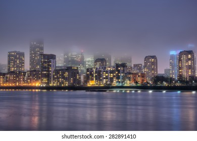 Night view over river Thames to foggy Canary Wharf