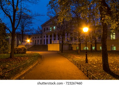 Night view of park, footpath and building of State University of Communication in Yusupov Garden, Saint Petersburg, Russia