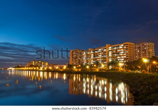 Night view of peaceful residential district with reflection in lake.