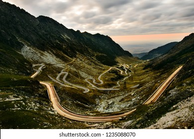 Night view of picturesque Transfagarasan Highway serpentine panorama in Romania Carpathians shined with car light trails taken from high viewpoint at Balea lake