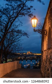 Night view of Prague from Vysehrad with bridges over Vltava river, Prague castle in the background in the evening and a lantern in the foreground. Prague. Czech Republic.