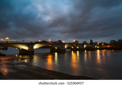 A night view of Putney bridge in London with light reflection in the river Themes