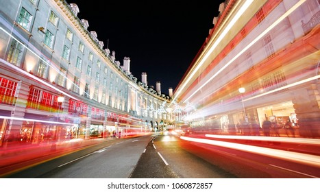 Night view of Regent Street with Christmas Lights. Since the time's bit late shopping street and traffice road looks quiet and empty. Fast moving bus's shown as light trails.
