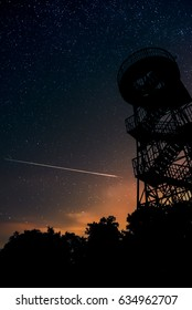 night view of shooting star on northern sky with silhouette metal observatory and woods