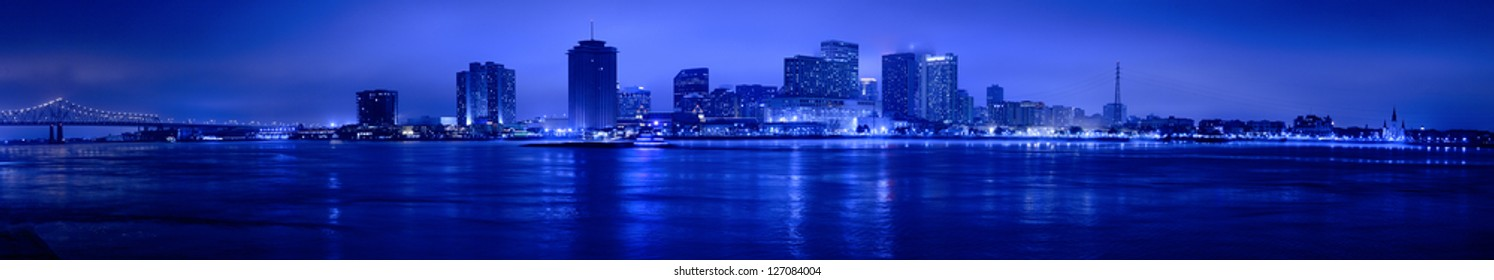 Night view of Skyline of New Orleans as seen from the MIssissippi river, including central business district, bridge and French Quarter