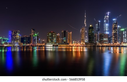 Night view of the skyscrapers of downtown Dubai and their reflection in the water.